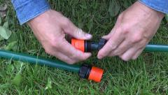 Gardener hands connecting watering hose on lawn Stock Footage