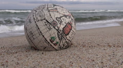 Retro globe map sphere on  ocean beach by water Stock Footage