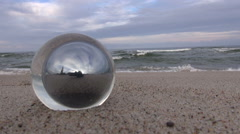 Reflection in round glass object placed in sand at the beach Stock Footage