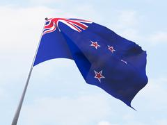 New Zealand flag flying on clear sky. - stock illustration