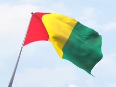 Stock Illustration of Guinea flag flying on clear sky.