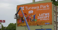 Two Men Workers in Truck Tower Are Installing an Orange Advertisement Banner - stock footage