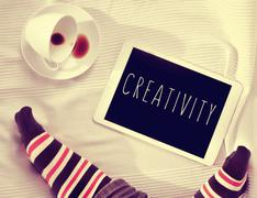 word creativity in a tablet computer on the bed, filtered - stock photo