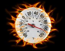 Round thermometer on fire - stock photo