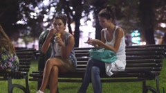 Teen age girl smoking and eating ice cream on evening time park bench - stock footage