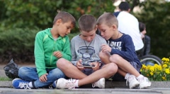 Three kids boys play one smart phone game sitting in a park public place Stock Footage