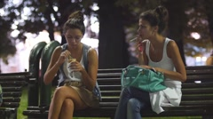 Teen age girl lights a cigarette and began to smoke on public evening park bench - stock footage