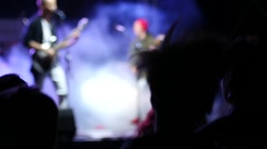 Jumping fans spectators silhouettes in lumiere flash by a rock concert stage Stock Footage