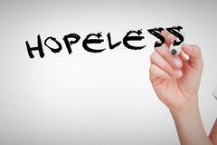 Stock Photo of Hopeless against female hand holding whiteboard marker