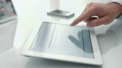 Lateral dolly of a man working in an office desk with a tablet.  - stock footage