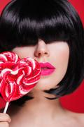 Closeup photo of a beautiful sexy pink lips with lollipop on red Stock Photos