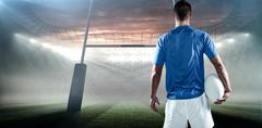 Composite image of rear view of rugby player holding ball aside Stock Photos