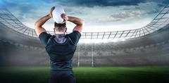 Stock Photo of Composite image of tough rugby player throwing ball