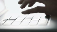 Female hands typing on a laptop. Backlit. Lateral dolly. Stock Footage