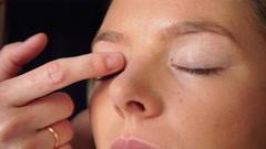 Makeup artist applying cream base to model eye 4K Stock Footage