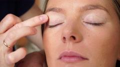 Stock Video Footage of Makeup artist applying cream base to model eye 4K