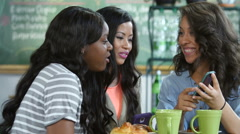 Ethnically diverse young women using a cell phone in a cafe Stock Footage