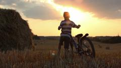 Boy with the bicycle in the field at sunset, near haystacks Stock Footage