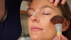 Makeup artist applying powder to model face 4K Stock Footage