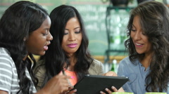 Ethnically diverse young women sharing a tablet/ipad in a cafe, close up Stock Footage