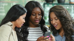 Three ethnically diverse young women using a cell phone in a cafe Stock Footage