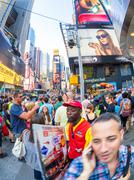 Tourists and locals crowd at famous Times Square in New York Stock Photos