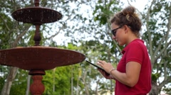 Young Female Using Digital Tablet in Park in Summer - stock footage