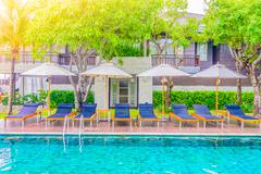 Outdoor Swimming pool and umbrella with chair deck in hotel resort for summer - stock photo