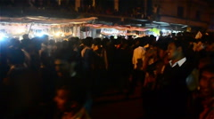 Slow pan shot of Indian people walking in a village fair. Stock Footage
