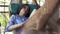 Young, pretty woman sleeping on hammock on terrace Stock Footage