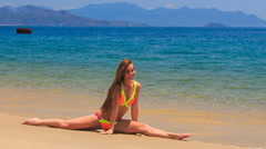 Blond girl in bikini sits in split on wet sea sand waves wash Stock Footage