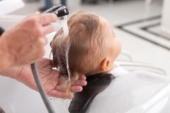 Experienced young barber is washing human head - stock photo