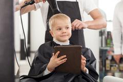 Cheerful young hairdresser is working with hair-drier Stock Photos