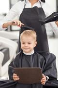 Skilled young hairdresser is serving her client Stock Photos