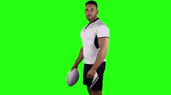 Serious rugby player holding ball - stock footage