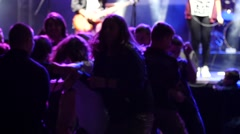 Slam on rock concert - crowd teen silhouettes push knock each other by a stage Stock Footage