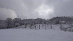 4K Heavy snow fall rural mountain village farm orchard tree winter season peace Stock Footage