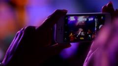 Spectator woman shooting photo via smart phone camera of concert rock band Stock Footage