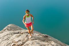 Skyrunner girl runs on a stony back over a lake Stock Photos
