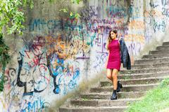Young woman down stairs next to murals - stock photo