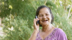 60 years old Thai woman smiling while talking on mobile phone Stock Footage
