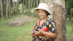 60 years old Thai woman smiling while using smartphone Stock Footage