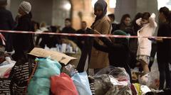 Syrian Refugees Listening to Announcement at Charity Collecting Point in - stock photo