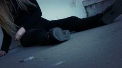 Drug addict girl sitting unconscious alone, syringe near, dolly. Stock Footage