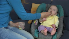 Baby girl eating food mash from mother hands with spoon. 4K Stock Footage