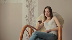Girl on armchair, rocker with remote control Stock Footage