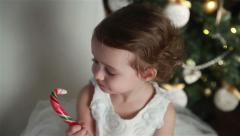 Little cute girl with a big Christmas candy. Stock Footage