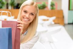 Pleasant girl holding packages Stock Photos