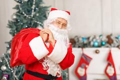 Santa Claus holding Christmas bag - stock photo