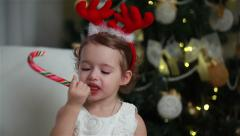 Stock Video Footage of Little cute girl eating a piece of candy on the eve of Christmas
